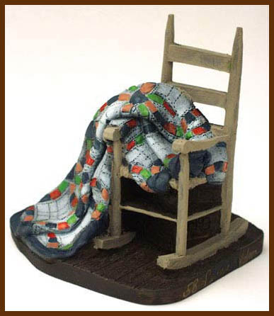 Small sculpture featuring a rocking chair with a double wedding ring quilt.