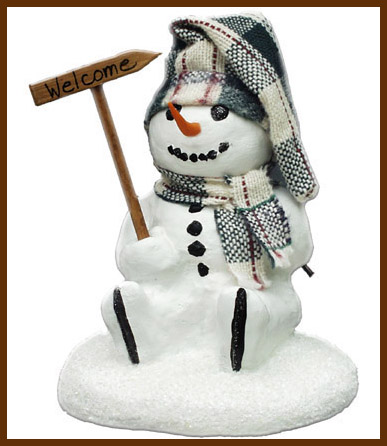 "A small sculpture featuring a ""Happy"" snowman holding a welcome sign."