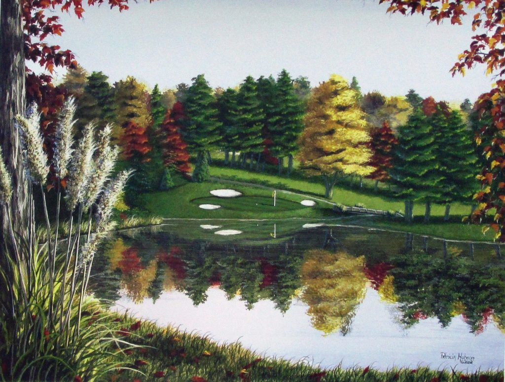 This fall golf print features the 17th hole at the Yadkin Country Club in Yadkinville, North Carolina. The green lies across the lake on a slope. The the golf green and fall leaves of the trees are reflected in the lake.