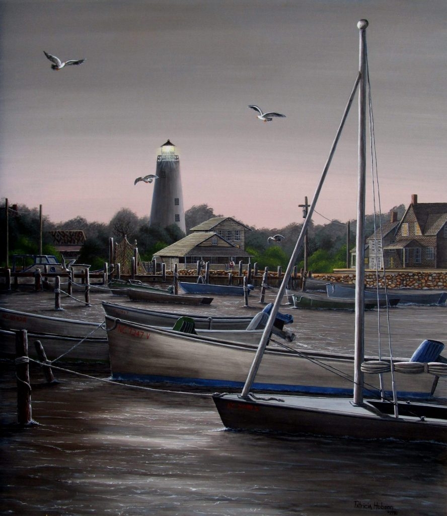 This a romantic evening view of the Ocracoke Lighthouse and village as scene through the boats from the water on the coast of North Carolina.