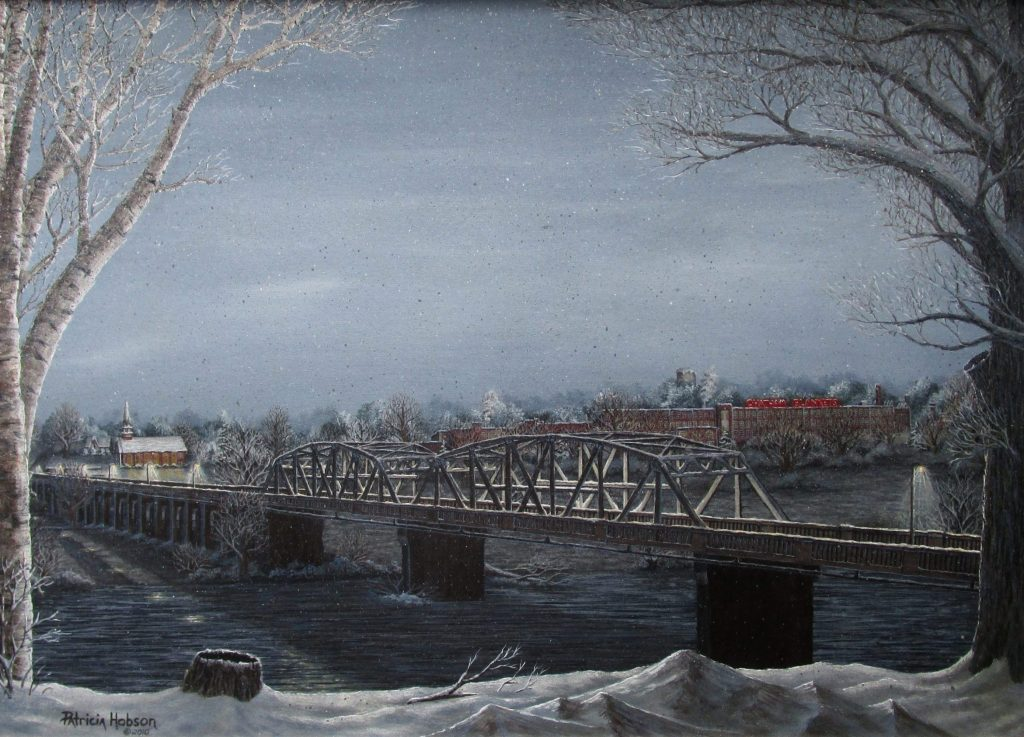 This snow scene features the Hugh Chatham Bridge crossing over the Yadkin River on a cold snowy evening with the lights reflecting on the snow, the church lights are on and the Chatham Blanket sign Glows red.