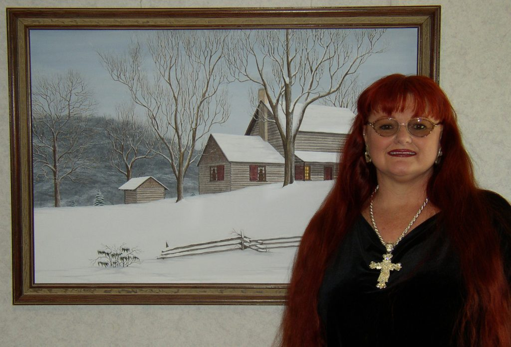 This a picture of Patricia Hobson with a beautiful painting that she did of the birth place of the late Governor Zebulan Vance of North Carolina